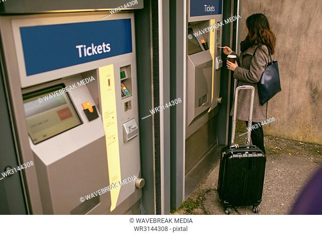 Woman taking ticket from machine