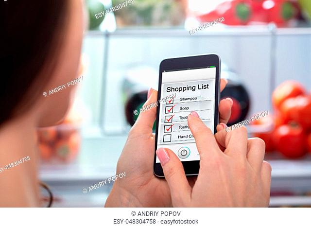 Close-up Of A Woman's Hand Marking Shopping List On Mobile Phone