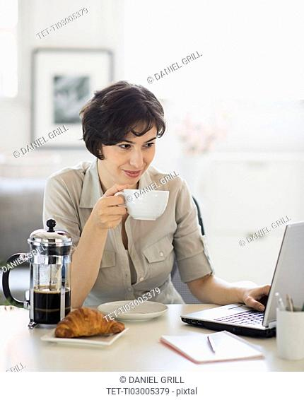 Portrait of woman having coffee and using laptop