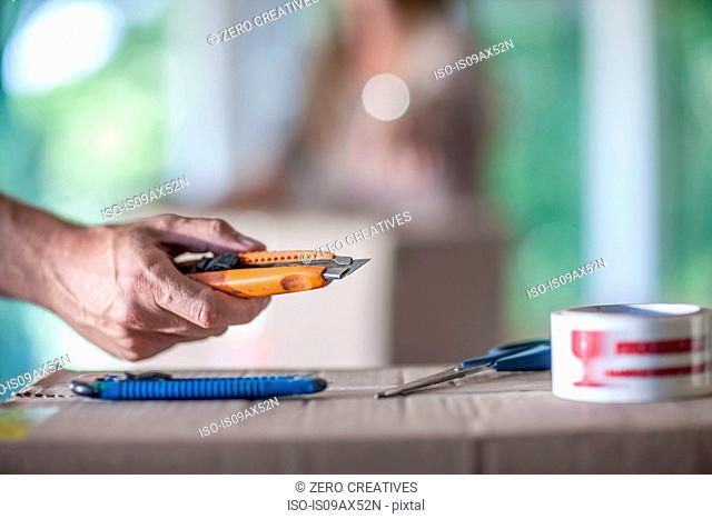 Moving house: man holding utility knife, close-up