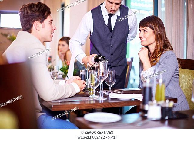 Waiter pouring wine for business associates at hotel restaurant