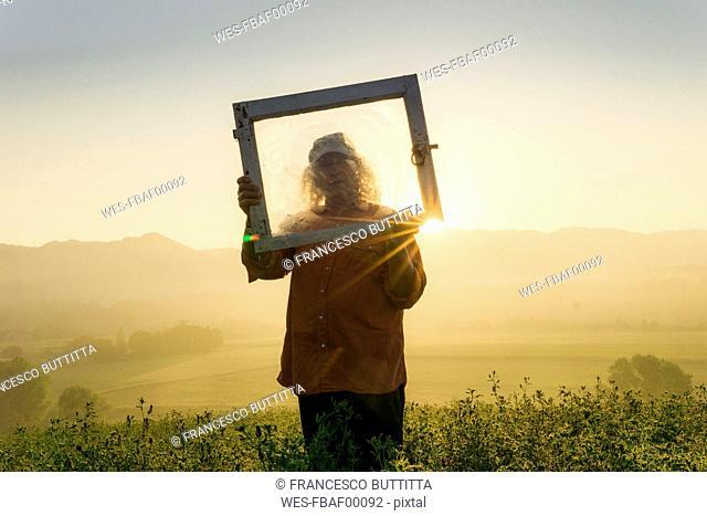 Italy, Tuscany, Borgo San Lorenzo, senior man holding window frame in field at sunrise above rural landscape