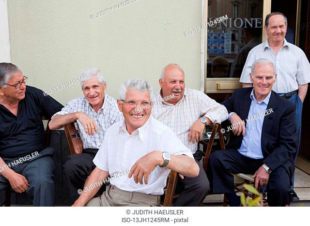 six old men sitting outside, laughing
