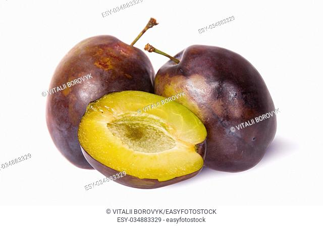 Two violet plums and half isolated on white background