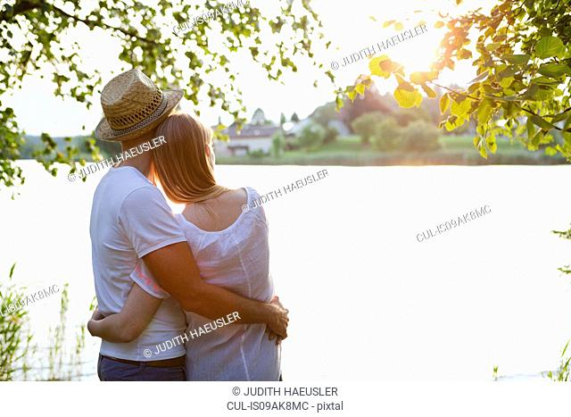 Rear view of mid adult couple watching sunset over lake