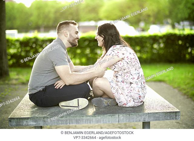 enamoured couple sitting together on ping-pong table, looking at each other