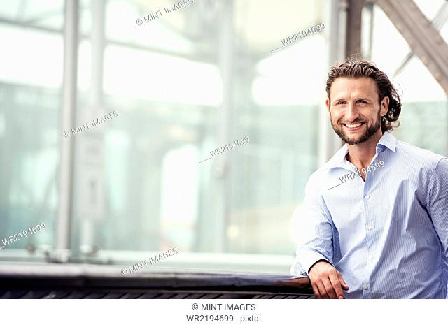 A man standing outdoors leaning on a windowsill, smiling