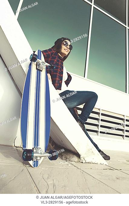 From below shot of female in sunglasses sitting on stairs with skate