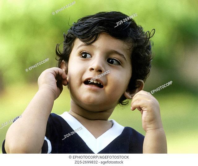 A little boy pulls his ears