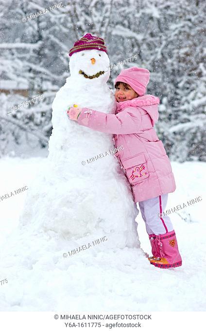 Little girl embracing snowman, smiling, portrait