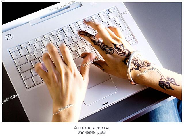 Hands of a young woman with a henna tattoo on the right hand typing in a laptop