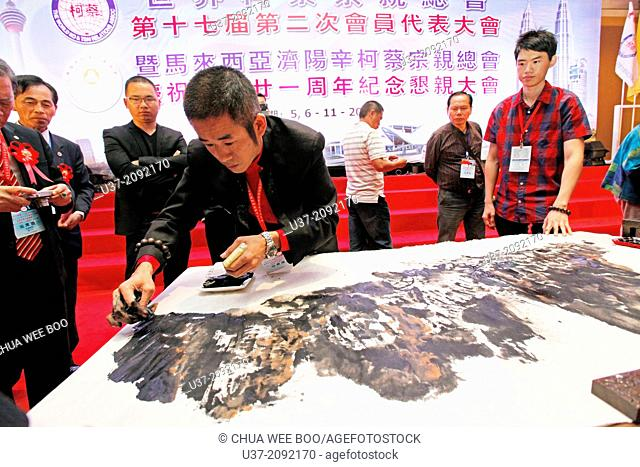 An talented artist paints with his hand for The World Chai's Clan 17th Anniversary at Genting Highland Convention, Malaysia