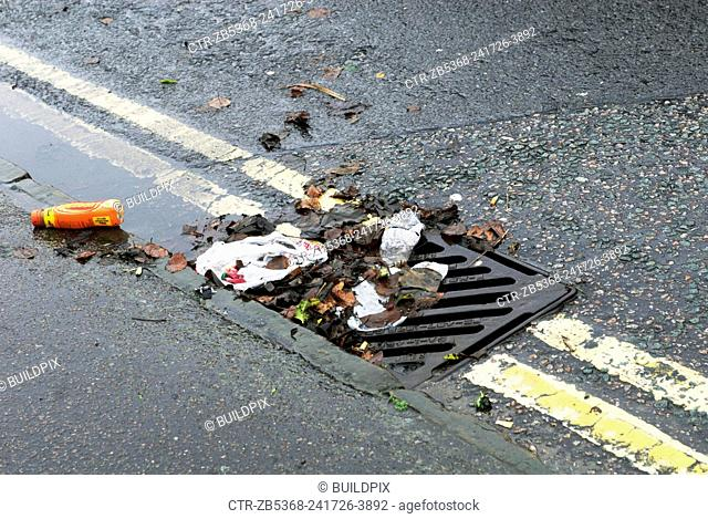 Litter, leaves and puddle in gutter by drain
