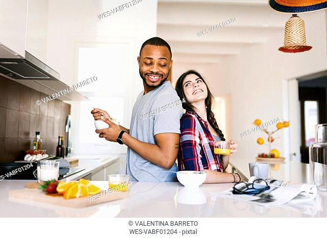 Young couple having breakfast in the kitchen, standing back to back