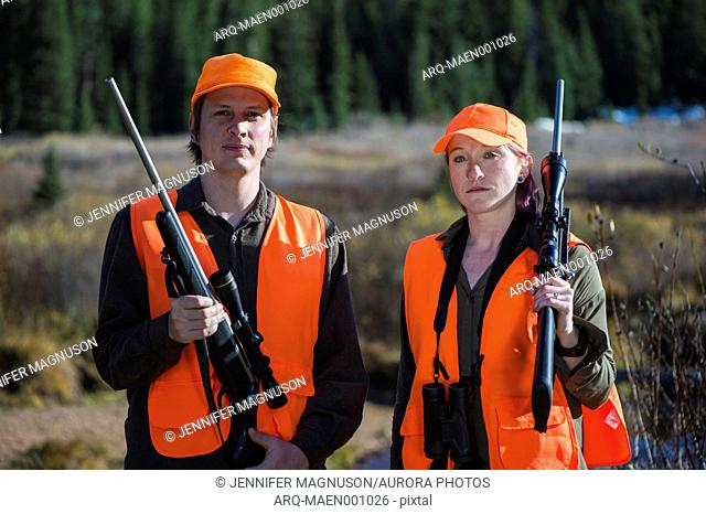 Portrait of male and female hunter posing with hunting rifles, Colorado, USA