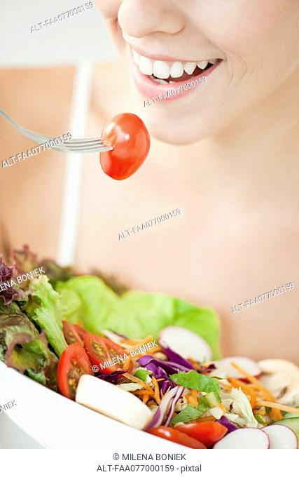Woman eating salad, cropped