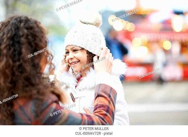 Mother putting knit hat on smiling daughter