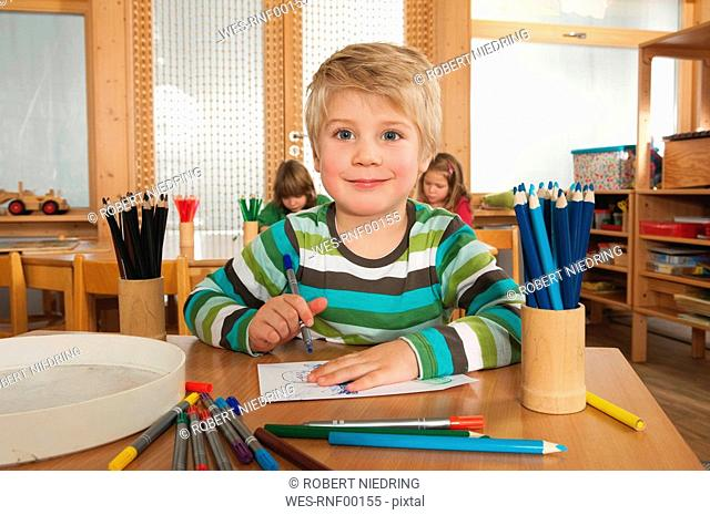 Germany, Children in nursery, boy 4-5 in foreground holding felt-tip pen, smiling, portrait