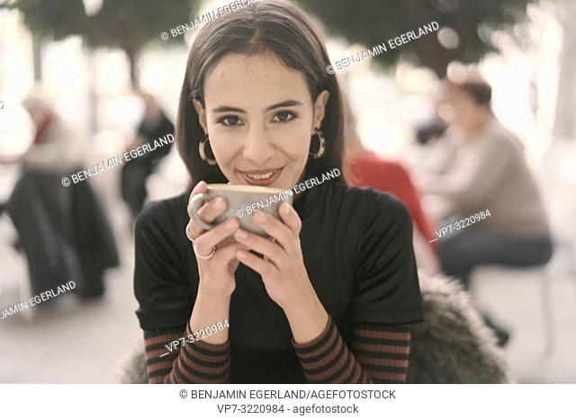 portrait of smiling woman holding coffee cup while sitting at table in restaurant, in Munich, Germany