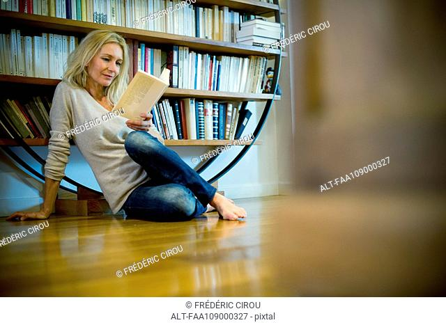 Mature woman relaxing with book at home