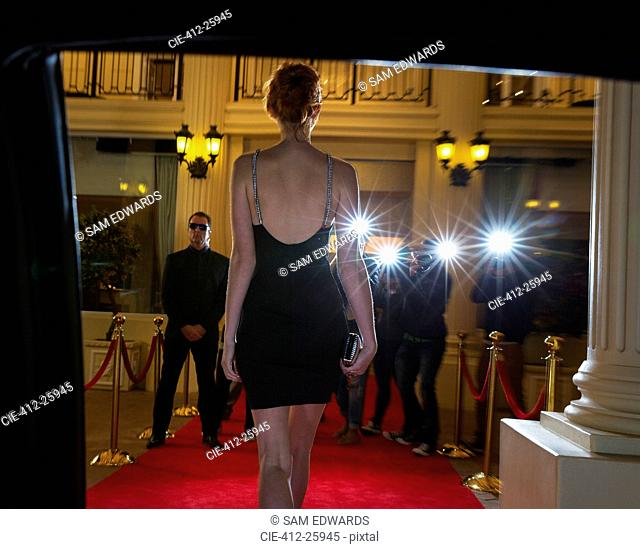 Silhouette of celebrity in black dress arriving at red carpet event