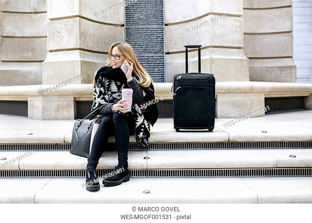 Young woman with luggage on cell phone on stairs