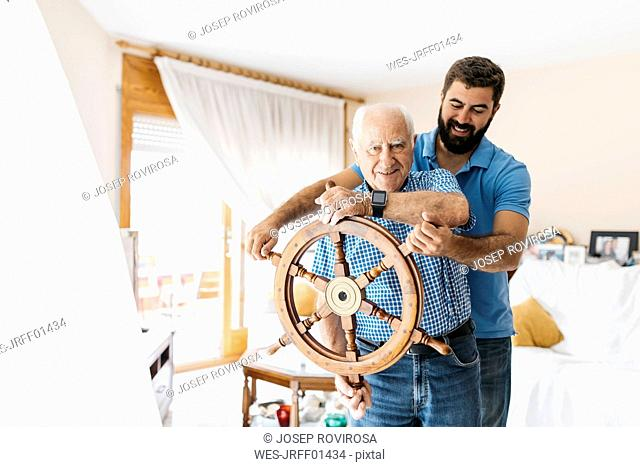 Portrait of grandfather and adult son with helm in the living room