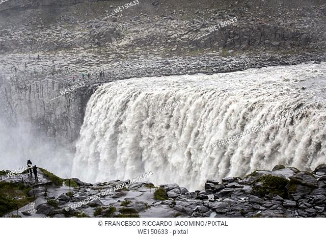 Iceland, a tourist admiring the power of Dettifoss waterfall