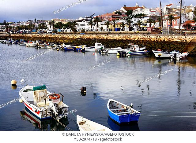 Boats port and view for Avenida dos Descombrimentos - main promenade of Lagos city, in background old town and Sao Sebastiao church on the hill, Algarve