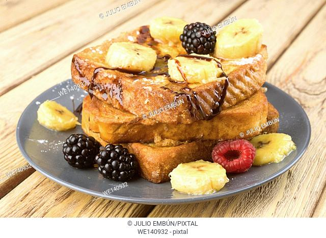 French toast with banana and berries on wood