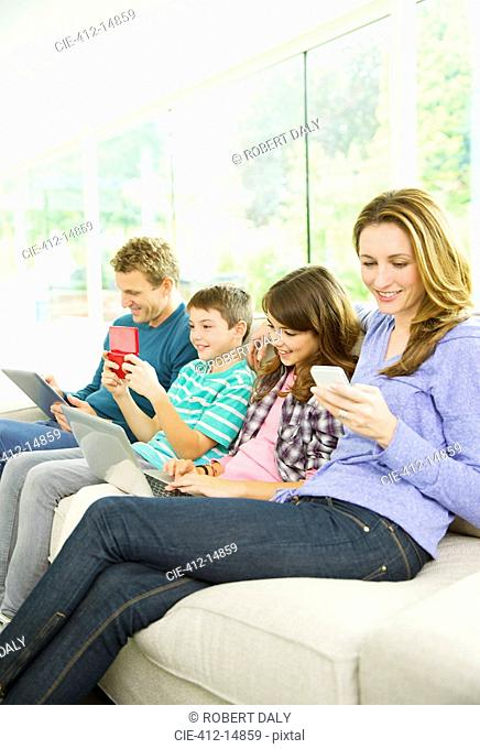 Family using technology on sofa