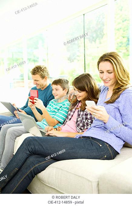Family using technology on sofa