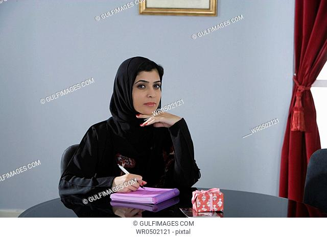 Arab woman writing a note together with her gift