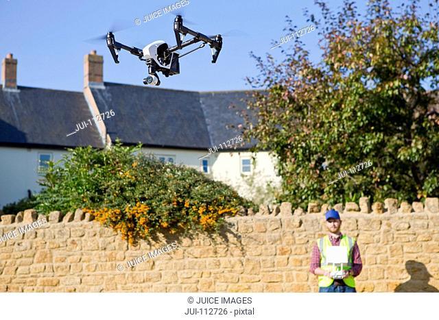 Surveyor operating surveillance drone in blue sky