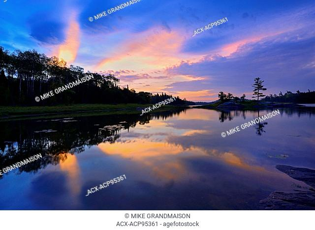 Clouds reflected in Middle Lake at dawn Kenora Ontario Canada