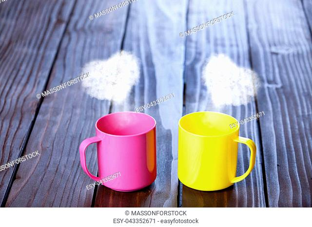 Two color cups of coffee with heart shape steams on wooden table