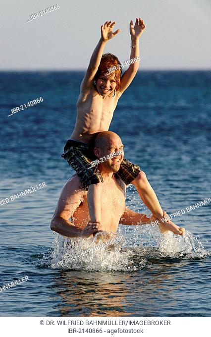 Father and son splashing around in the sea