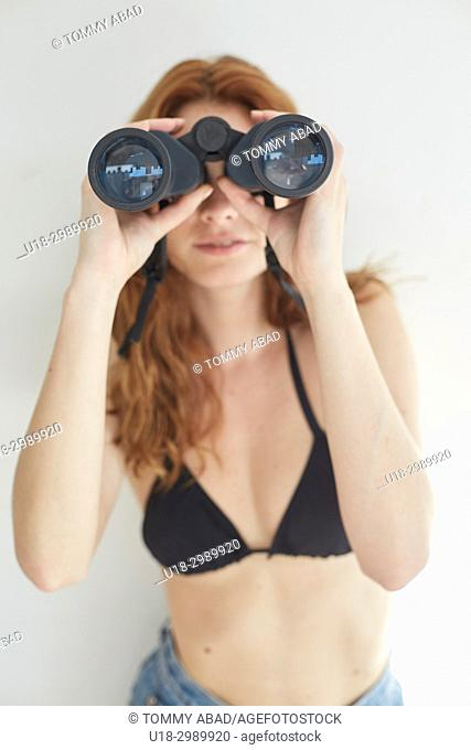 Young redhead woman using binoculars