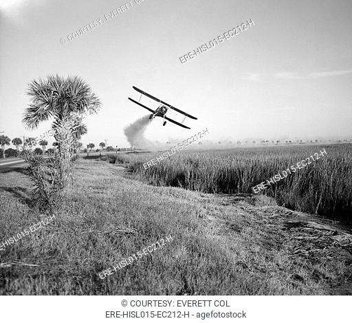 A bi-plane is spraying DDT insecticide during malaria control operations in Savannah, Georgia. Ca. 1950