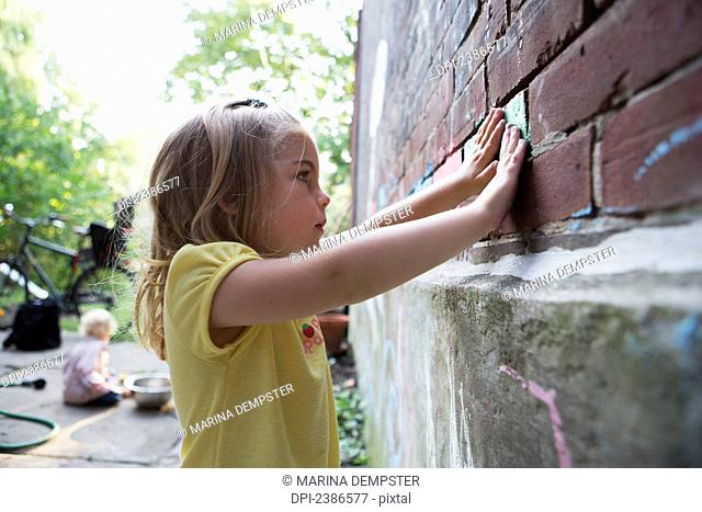 Young girl rubbing coloured chalk into brick wall outside in her garden with her brother sitting behind her; Toronto, Ontario, Canada