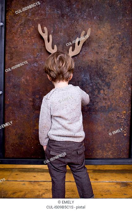 Young boy standing facing wall, cardboard reindeer cut out on wall behind him