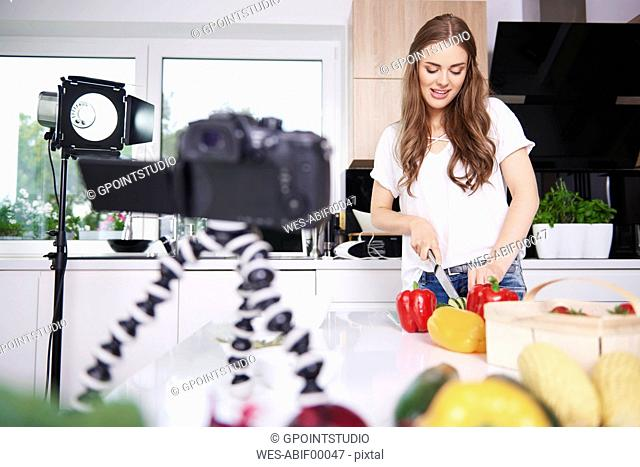 Woman recording while chopping vegetables