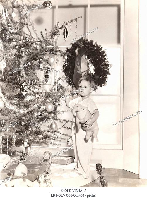 Little boy standing by tree on Christmas morning