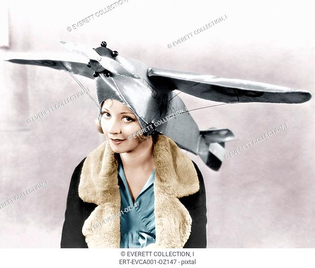 Portrait of a young woman wearing an airplane shaped cap Old Visuals