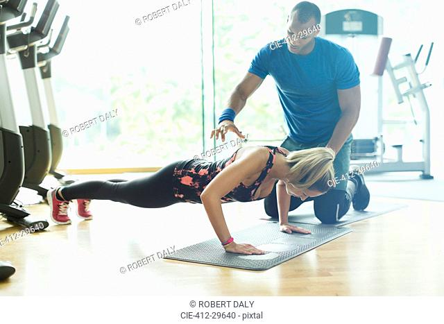Personal trainer guiding woman doing push-ups at gym
