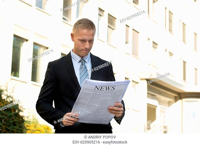 Portrait Of A Young Businessman Reading Newspaper