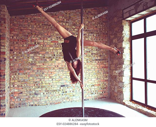 Young pole dancer woman trains on grunge interior with brick walls