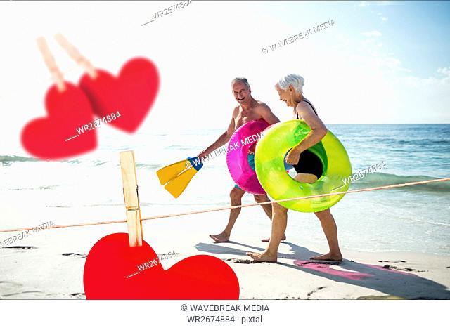Senior couple with swim ring and swimfin walking on beach