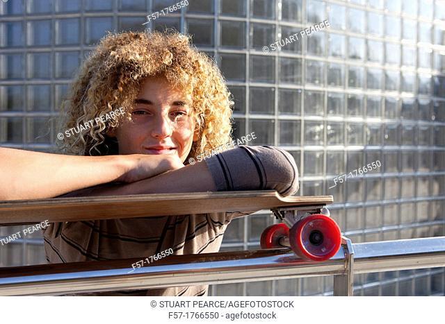 Teenage boy leaning on his skateboard