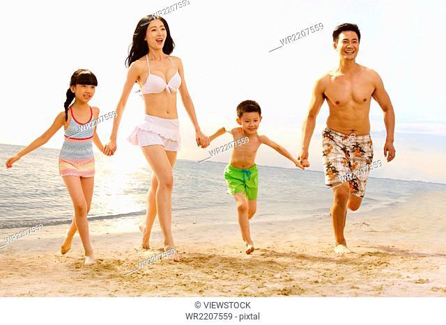 Family on beach in swimwear